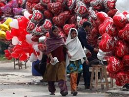 Ženy procházejí kolem prodavačů balónků s motivy svátku zamilovaných v