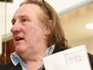 Gérard Depardieu ukazuje svůj ruský pas (23. února 2013).