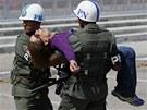 Policisté odnášejí ženu, která nevydržela únavné čekání před caracaskou