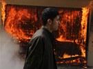 Muž prochází kolem hořícího policejního klubu v egyptské Káhiře.