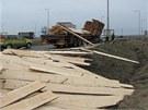 Z náklaďáku se na kruhovém objezdu vysypala většina dřevěných prken, které vezl.