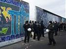 Policisté hlídají část Berlínské zdi, kterou stavaři bourali.