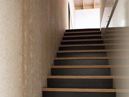 Přízemí spojuje s ložnicí a horní terasou uzavřené dřevěné schodiště.