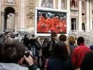 Lidé na náměstí svatého Petra ve Vatikánu sledují přenos z kardinálské