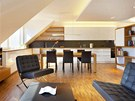 """Byt 1: Barevnost obývacího pokoje s kuchyní vychází ze zásady, že bílá barva stěn nepohlcuje světlo a pokoj opticky zvětšuje. Dřevěná podlaha působí na psychiku jako pevná, """"stabilní""""."""