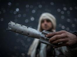 Syrský povstalec ukazuje zbytky vládního granátu (leden 2013)