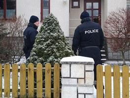 Policisté hlídkují před domem zavražděných manželů v Městě Albrechticích. (13.
