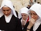 Katolické řádové sestry se modlí po příchodu procesí.