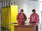 Pracovníci elektrárny v ochranných oblecích a rouškách.