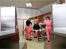 Pracovníci elektrárny se oblékají do ochranných kombinéz.
