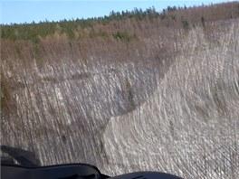 Pohled z kabiny záchranářského vrtulníku na úbočí Velkého Javorníku. Les byl na