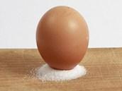 Vejce na špičce ve velké hromádce soli.