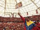 Nicolas Maduro mává před svými příznivci portrétem Huga Cháveze (30. března