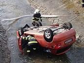 Havarované auto z potoka vytáhli hasiči.