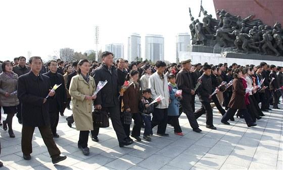 Severokorejci vyrážejí položit květiny před sochu uctívaného vůdce Kim Ir-sena.