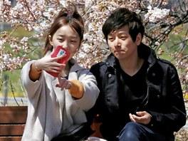 Dvojice sedí v parku v jihokorejském Soulu. Jeho obyvatele hrozby svého