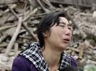 Žena před troskami domu zničeného při zemětřesení  v čínské provincii