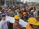 Bangladéští záchranáři vynášejí tělo jedné z obětí neštěstí, při kterém se...