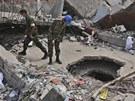 Bangladéšští záchranáři se snaží vyprostit z trosek zříčené budovy přeživší
