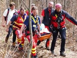 Záchranáři s členy Horské služby Beskydy přenášejí zraněnou pacientku.