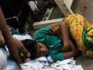 V textilní továrně se kromě práce i spí. Třeba i mezi šicími stroji.