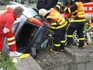 Hasiči a záchranář u auta v Ostravě, které zůstalo po smyku zaklíněné v