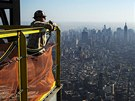 Jeden z dělníků sleduje centrum New Yorku ze střechy One World Trade Center....