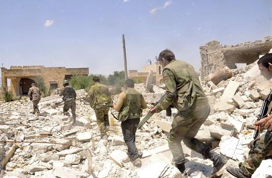 Jednotky loajální prezidentu Bašáru Asadovi pochodují zpustošenou krajinou.
