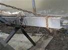 Zloději kovů si zbytek postupně odřezávané lávky řetězem přichytili ke břehu.