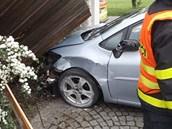 Toyota Auris se zasekla přímo mezi sloupky vrat.