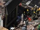 Hasiči odklízejí sutiny po pádu budovy v centru Filadelfie (5. června 2013)
