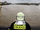 Člen pražského hasičského sboru pozoruje rozvodněnou Vltavu z uzavřeného