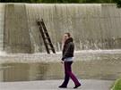 Žena pozoruje přetékající protipovodňovou hráz v Hoříně u Mělníka. (4. června