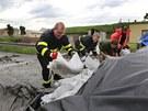 Hasiči v Terezíně připravují pytle s pískem.