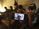 Vzpomínka na bratra. Náctiletý syrský povstalec ukazuje na mobilu snímek svého