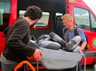 Pracovníci Člověka v tísni distribuují věci potřebné na odklízení škod po