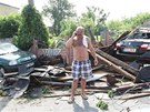 Josef Kobza u trosek střechy z jeho domu. Trámy zavalily i jeho auto (vlevo) a