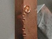 Krátery ma měděném terči vypálené pražským laserem PALS. Měď má sílu cca půl centimetru. Všechny krátery vznikly během jediného impulzu, každého trvajícího asi miliardtinu vteřiny. Největší (nahoře) vznikl během pulsu, který měl asi polovinu maximálního výkonu PALS, tedy cca 1,5 TW. Cílem experimentu bylo vytvoření měděného plazmatu a zkoumání jeho vlastností v rámci výzkumu zvládnutí jaderné fúze.