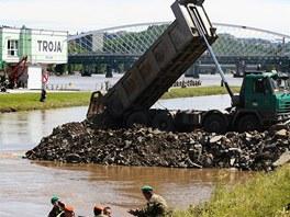 Vojáci navážejí suť, aby zahradili plavební kanál u Císařského ostrova v Praze