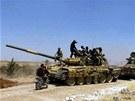 Syrští rebelové na tanku, kterého se zmocnili po dobytí vojenské základny Iskan