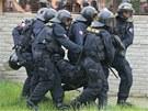Policisté odnášejí zraněného kolegu (29. června 2013).