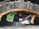 Hasiči odřezávají pod prostředním mostním obloukem v Ronově dřevěné bednění.