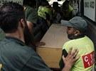 Pracovníci nemocnice a záchranáři nakládají truhly s těly horolezců zabitých