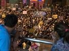 Lidé sledují protesty v Rio de Janeiru.