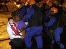 Demonstrant klečící na zemi brání postupu policejního kordonu v pondělí 24.