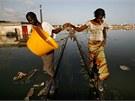 Dívky balancují na zatopených kolejích při povodních v Thiaroye Sur Mer na