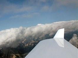Tam, co ukazuje winglet na konci křídla, je v mracích ukryt masív nejvyšší...