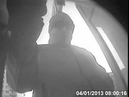 Jeden ze zlodějů při vybírání peněz z bankomatu.