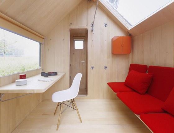Přední část slouží jako obývací pokoj: na jedné straně je rozkládací pohovka,