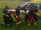 Hasiči a záchranáři nesou do vrtulníku mladou ženu, která se popálila, když se...